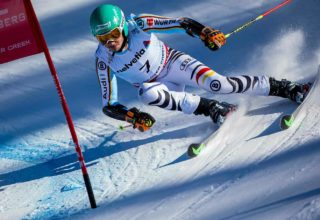 Competitive downhill skier racing towards flag
