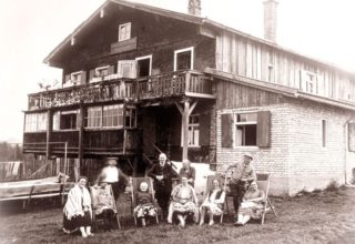 Family posing for photo outside hotel in 1928
