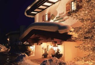 Exterior of Sonennalp Hotel restaurant at night, entrance awning filled with snow