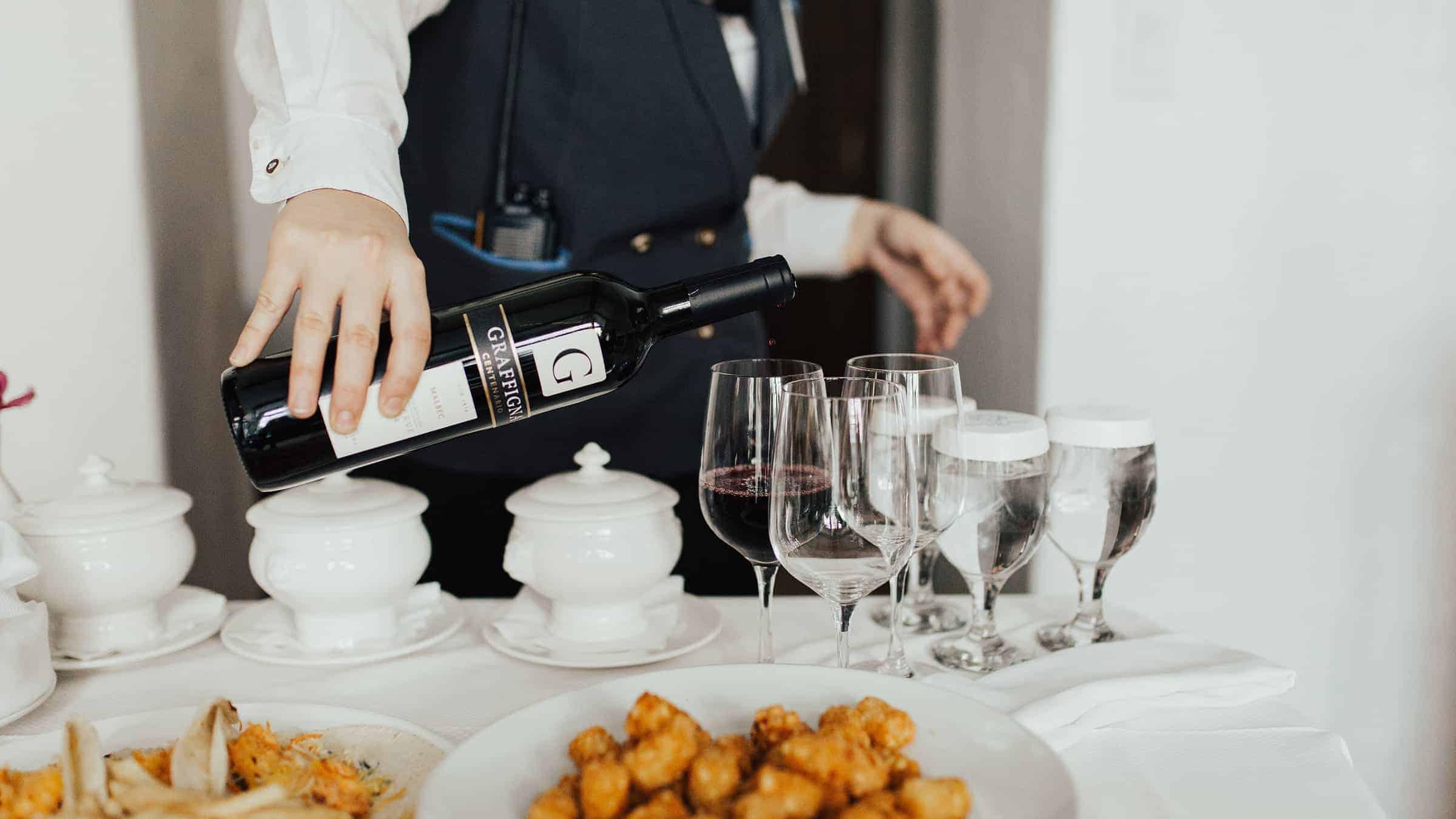 Server pouring wine into glasses