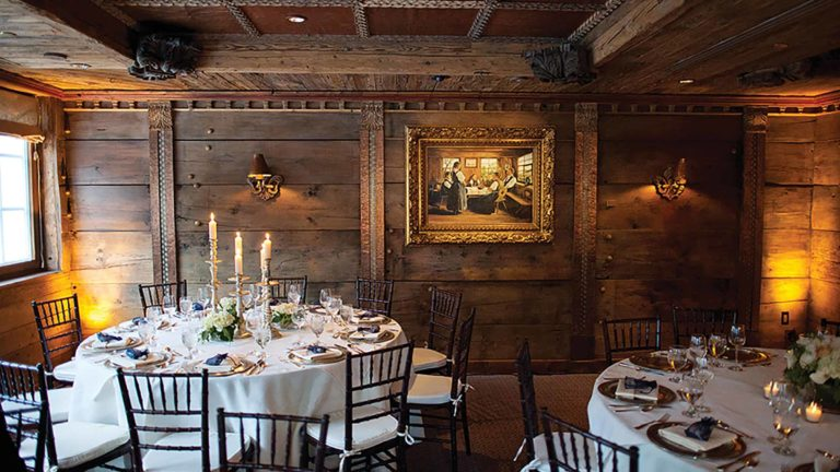Dining room with wooden walls and tables with placesettings