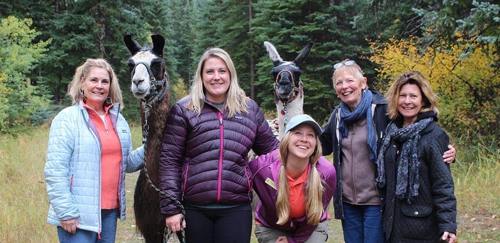 Women posing for photos with llamas