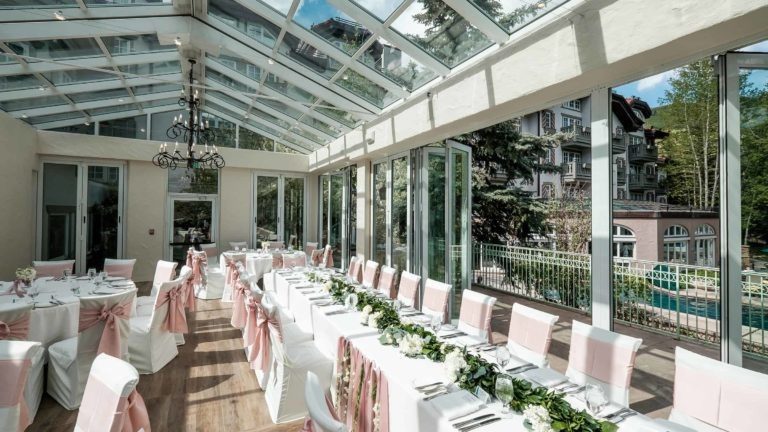 Outdoor terrace with long table and tables with placesettings