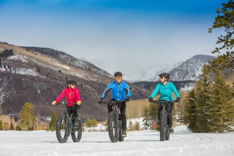 Three people on snow bycycles with fat tires