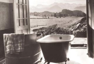 Room with two tubs, doors open, and view of trees and hills