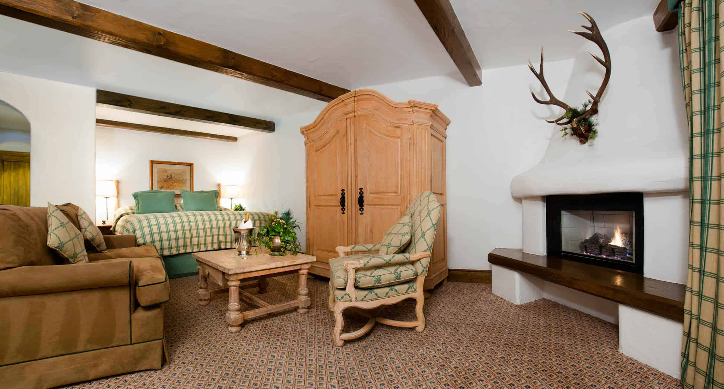 Suite with living room, fireplace, sofa, chairs, and armoire