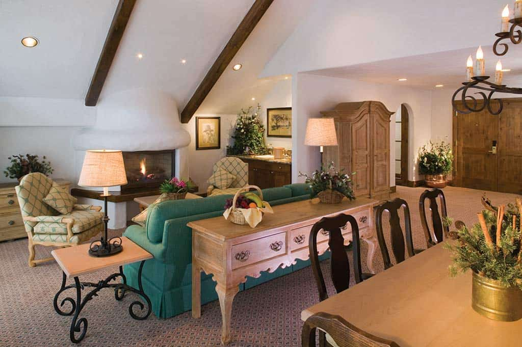 Suite living room with sofa, chairs, fireplace, and dining table and chairs in foreground