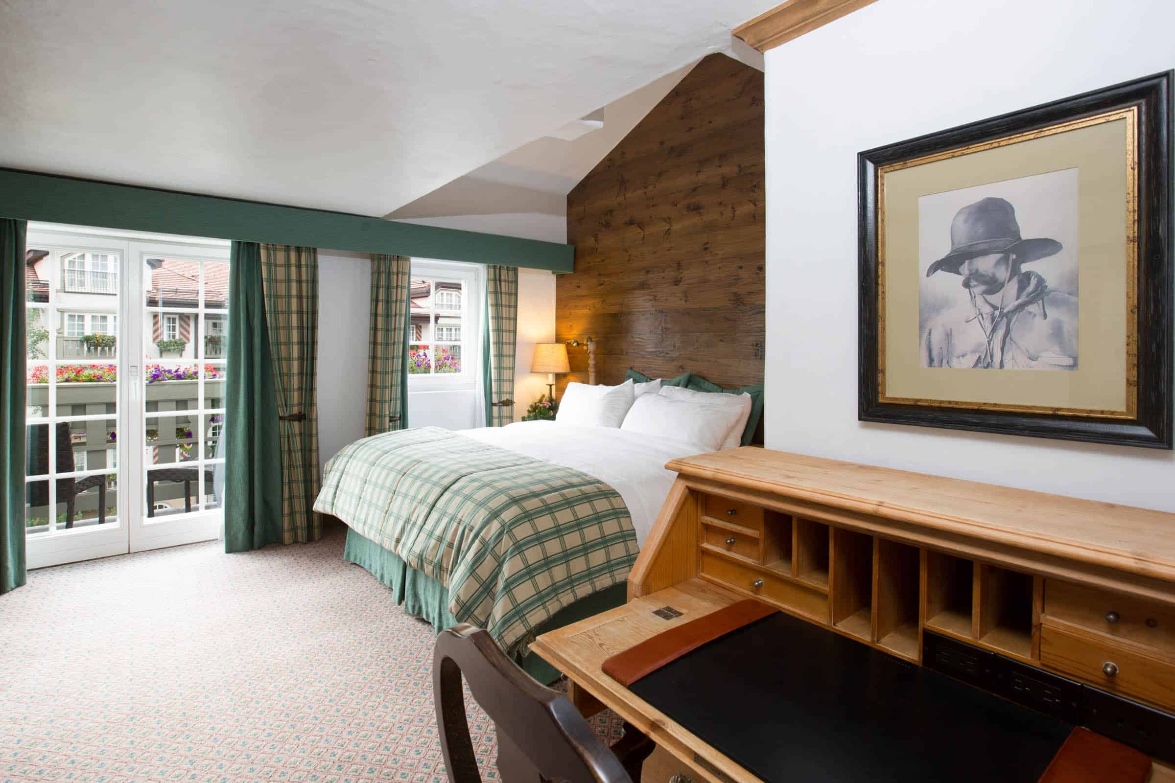 juniper room with bed, doors leading to balcony in background, desk and chair in foreground