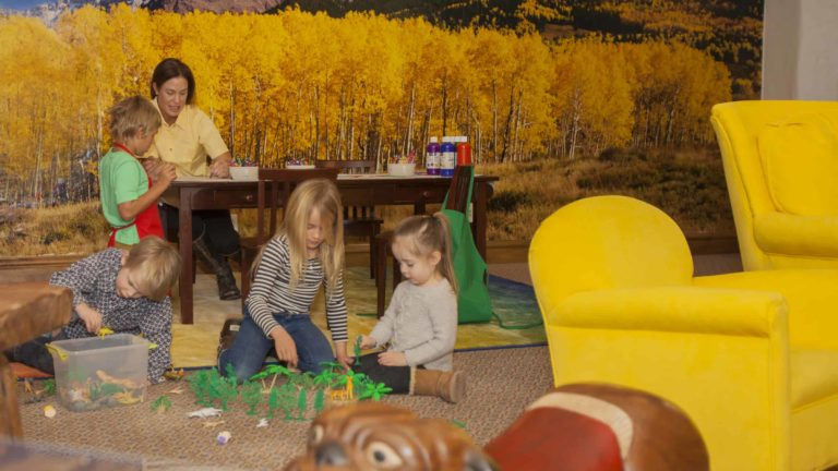 Children playing on carpeted floor and adult sitting at table helping a child paint with brush