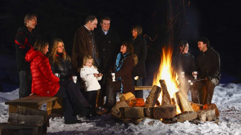 people gathered outdoors next to a firepit, some roasting marshmellows