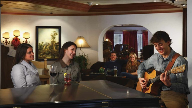 man playing guitar in lounge area as people listen