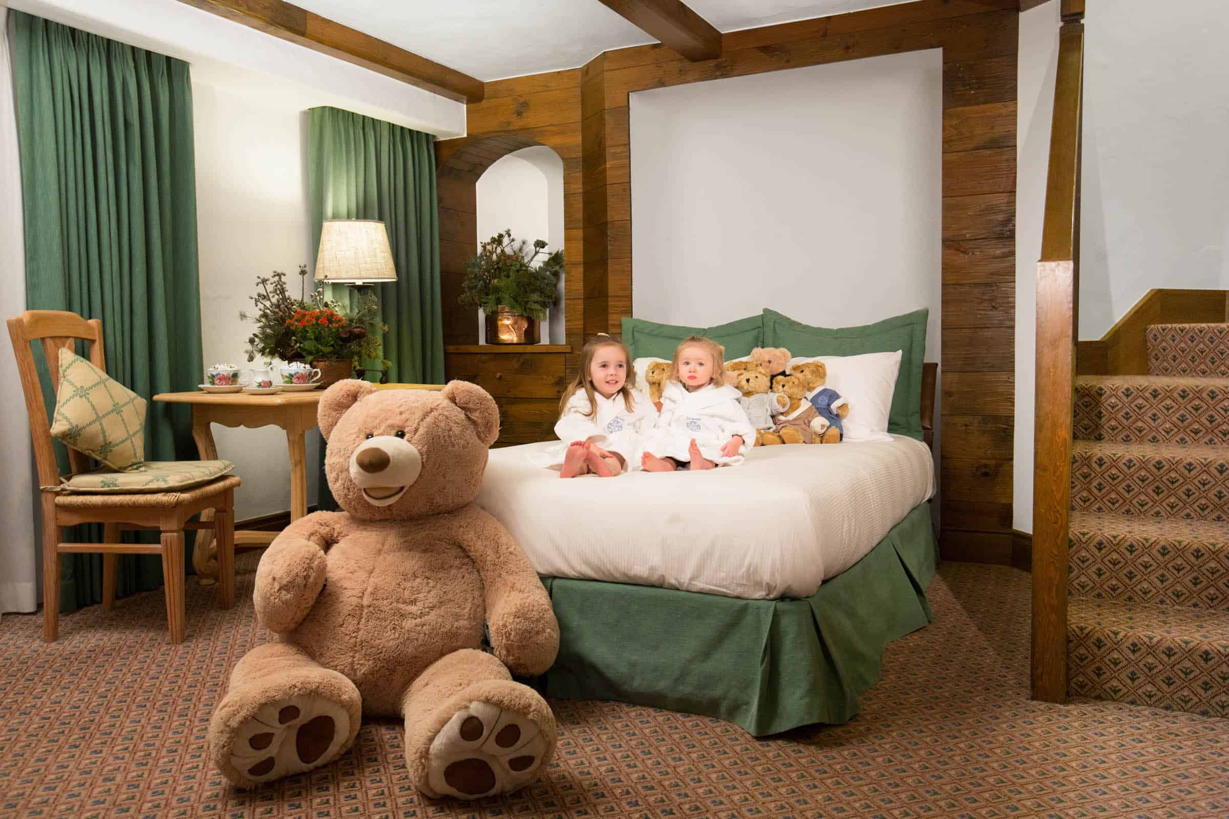 children wearing robes on bed and large teddy bear at the foot of bed