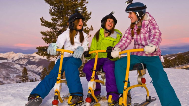 Women on snow cycles, on slopes, at dusk