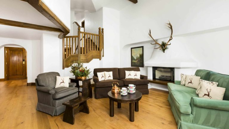 Living room with sofa, chairs, fireplace, and stairs