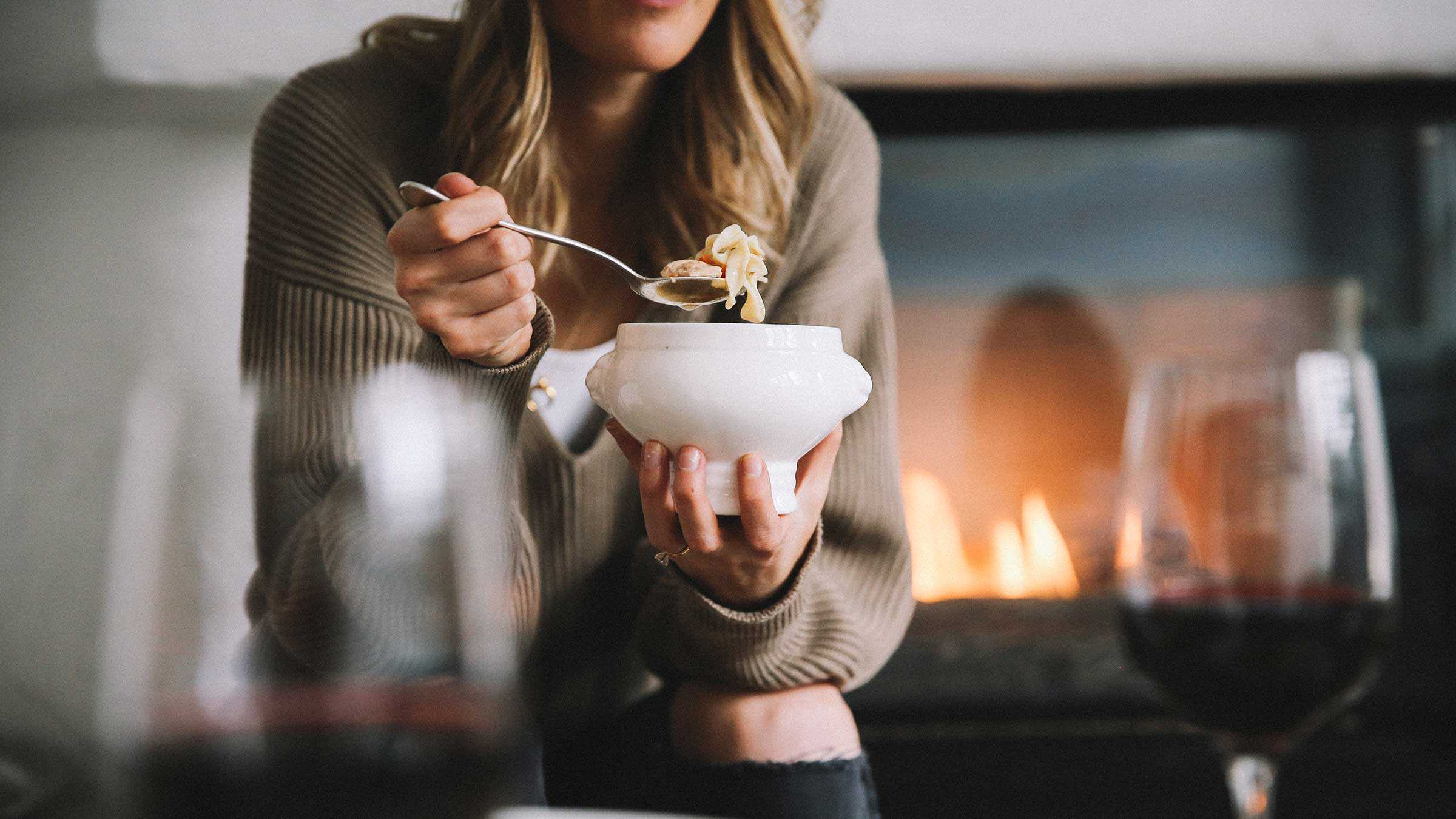 Woman eating noodle soup from a bowl, fireplace in the background