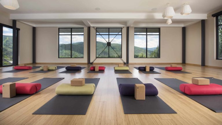 Room with large windows, hardwood floor, and yoga mats arranged in rows
