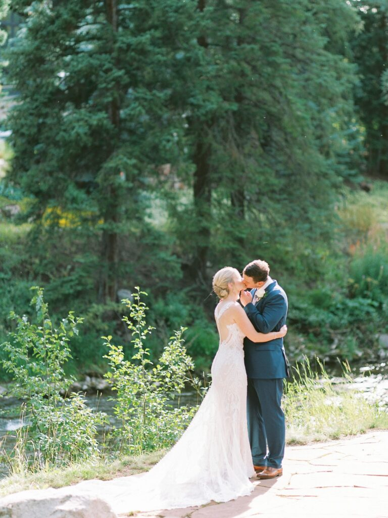 Bride and groom standing outdoors on a sunny day, next to a stream, kissing