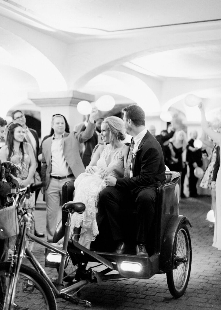 Wedding couple sitting on a rickshaw as wdding guests wave