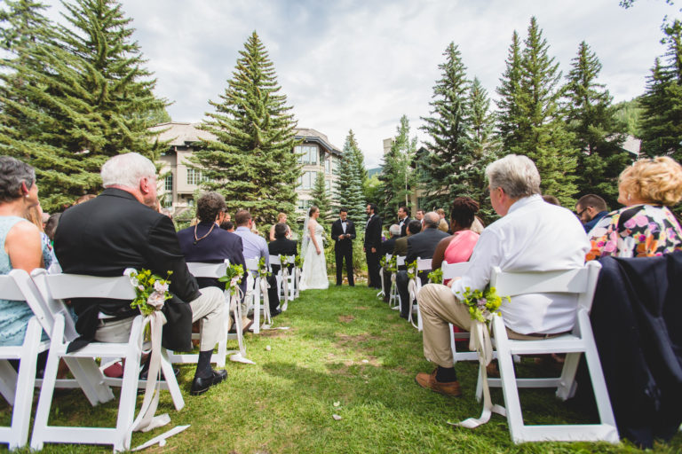 Outdoor wedding ceremony as seen from center aisle, behind seating area