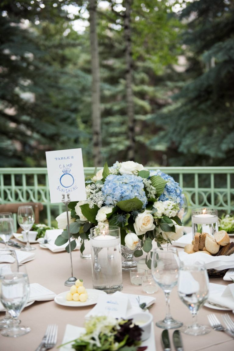 Closeup of outdoor table with centerpiece, various dishes, and place card