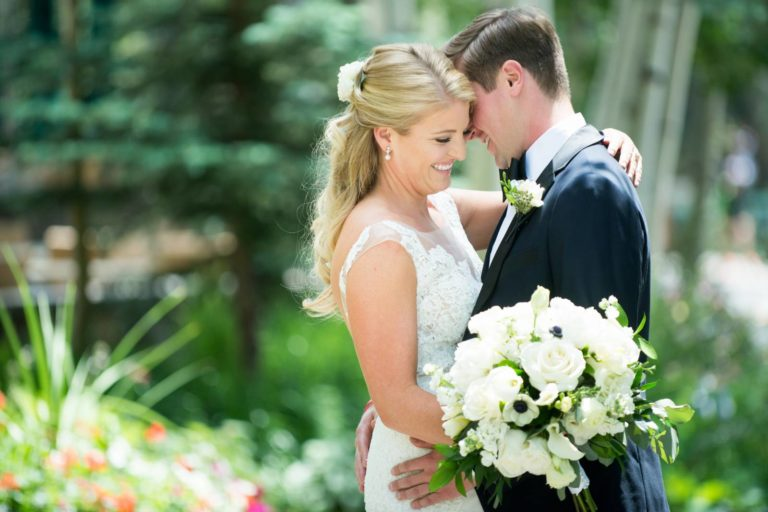Bride and groom embracing closely outdoors, bride holding a bouquet of flowers