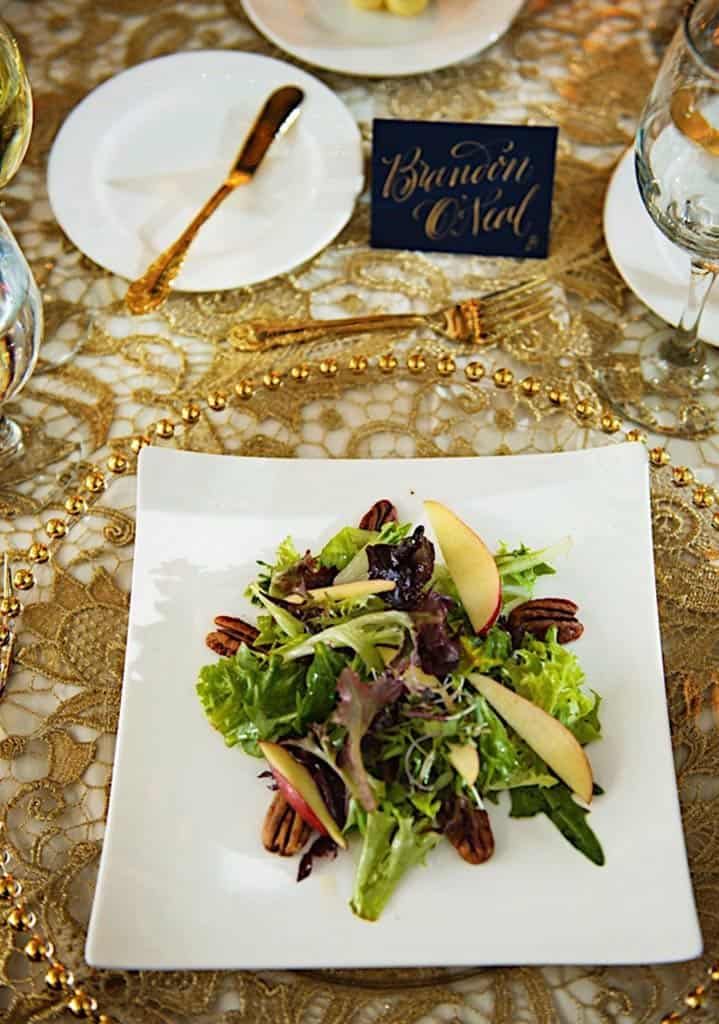 Closeup of square plate wth salad, and place card on tablke