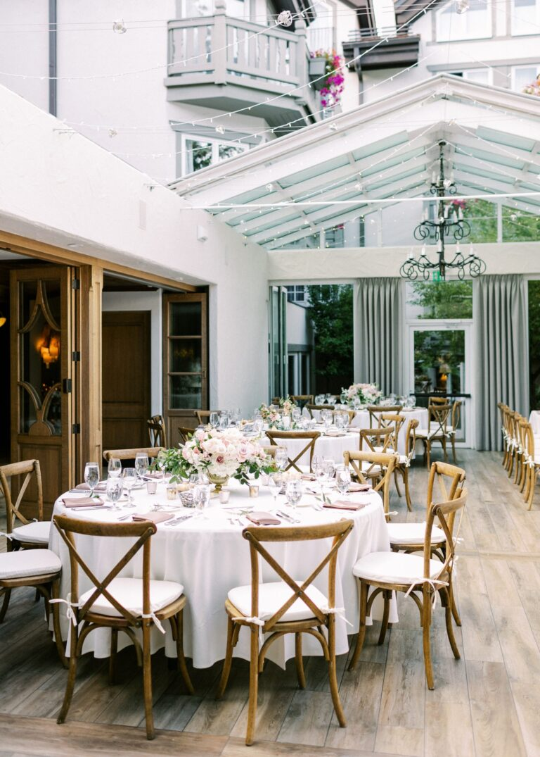 Wedding reception space with tables with placesettings and centerpieces