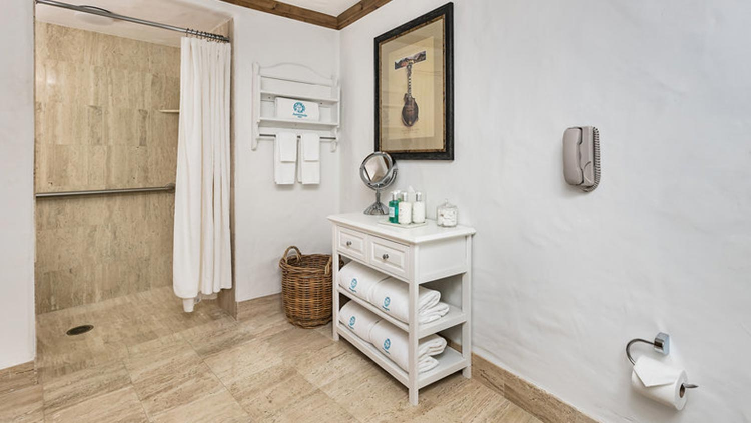 Bathroom with shower and small stand with drawers and towels underneath