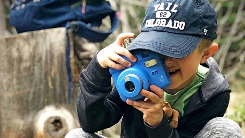 Child wearing a baseball hat taking a photo