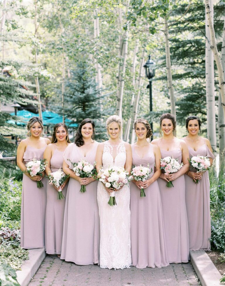Bride in the center, bridesmaids next to her, all holding flower bouquets
