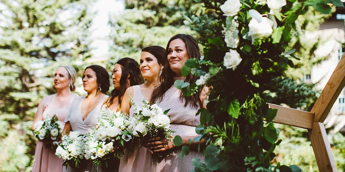 Bridesmaids holding flower bouquets outdoors