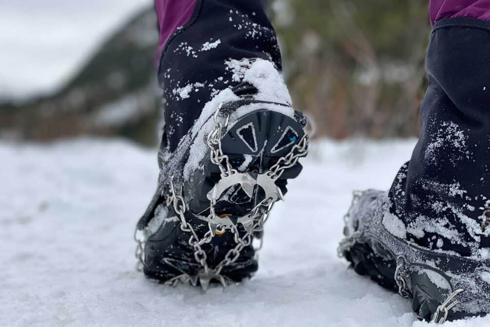 Closeup of person walking on ice, wearing shoes with snow chains and spikes