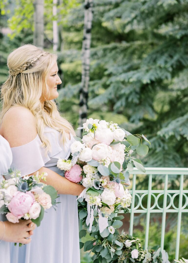 Bridesmaid holding floral bouquet, trees in the background
