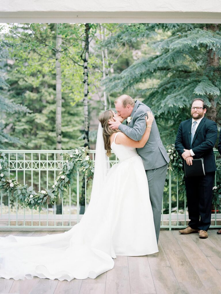 Bride and groom kissing in veranda, trees in the background, man holding porftolio next to couple