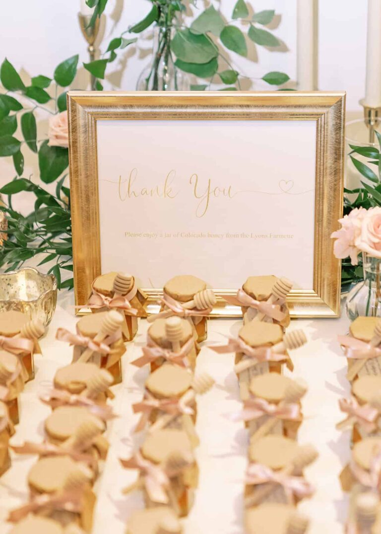 Frame with thank you sign and wedding favor honey jars in the foreground