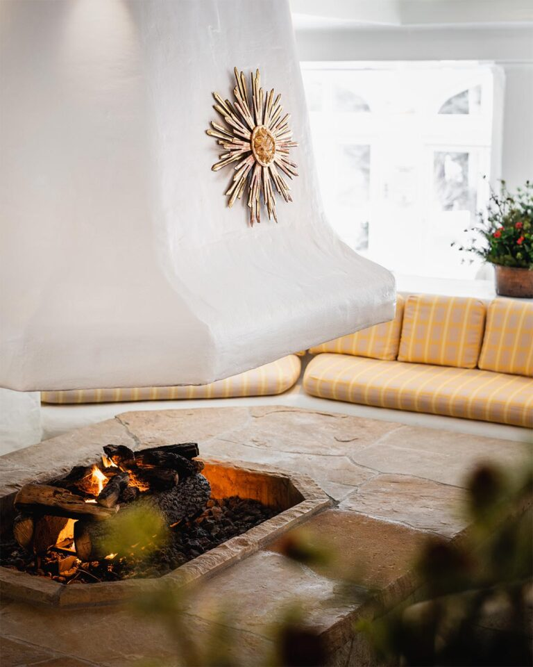Spa room with stone firepit and cushioned seating area around it