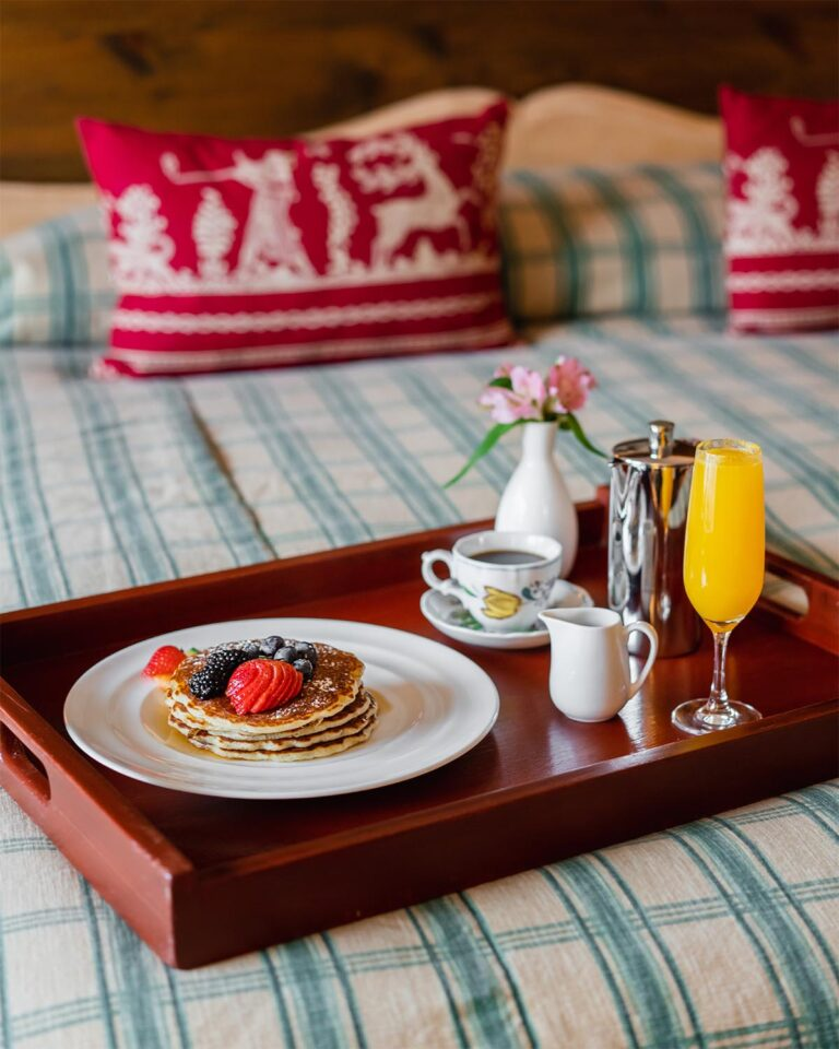 Breakfast tray on bed with plate with pancakes, cup with coffee, and flute with orange juice