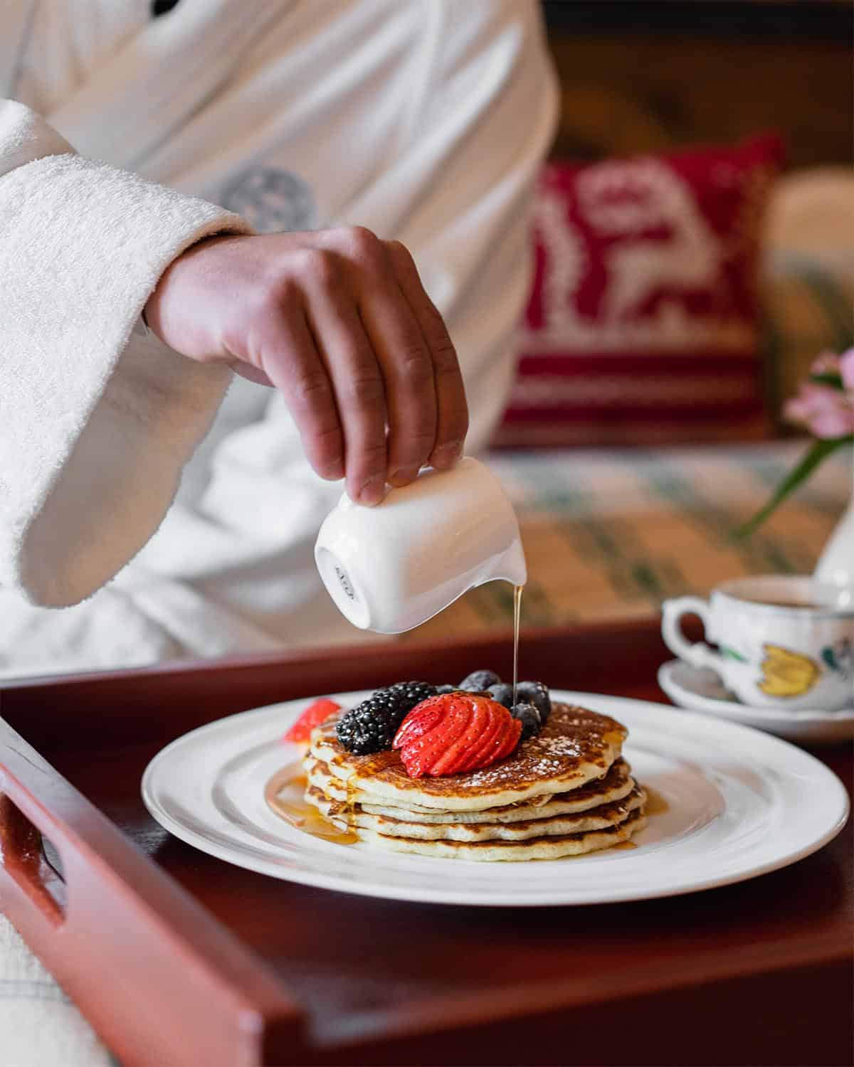 Person wearing bathroube pouring syrup over pancakes with fruit on tray on bed