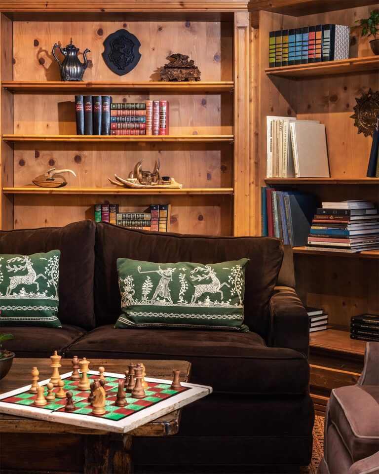 Sofa, coffee table with chessboard on foreground, and bookcase shelves in the background