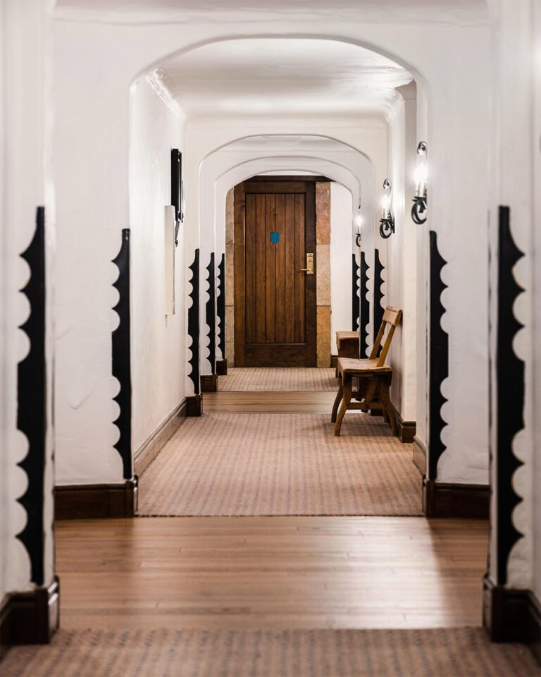 Hotel hallway with area rugs, wooden benches, and door at the end of the hallway