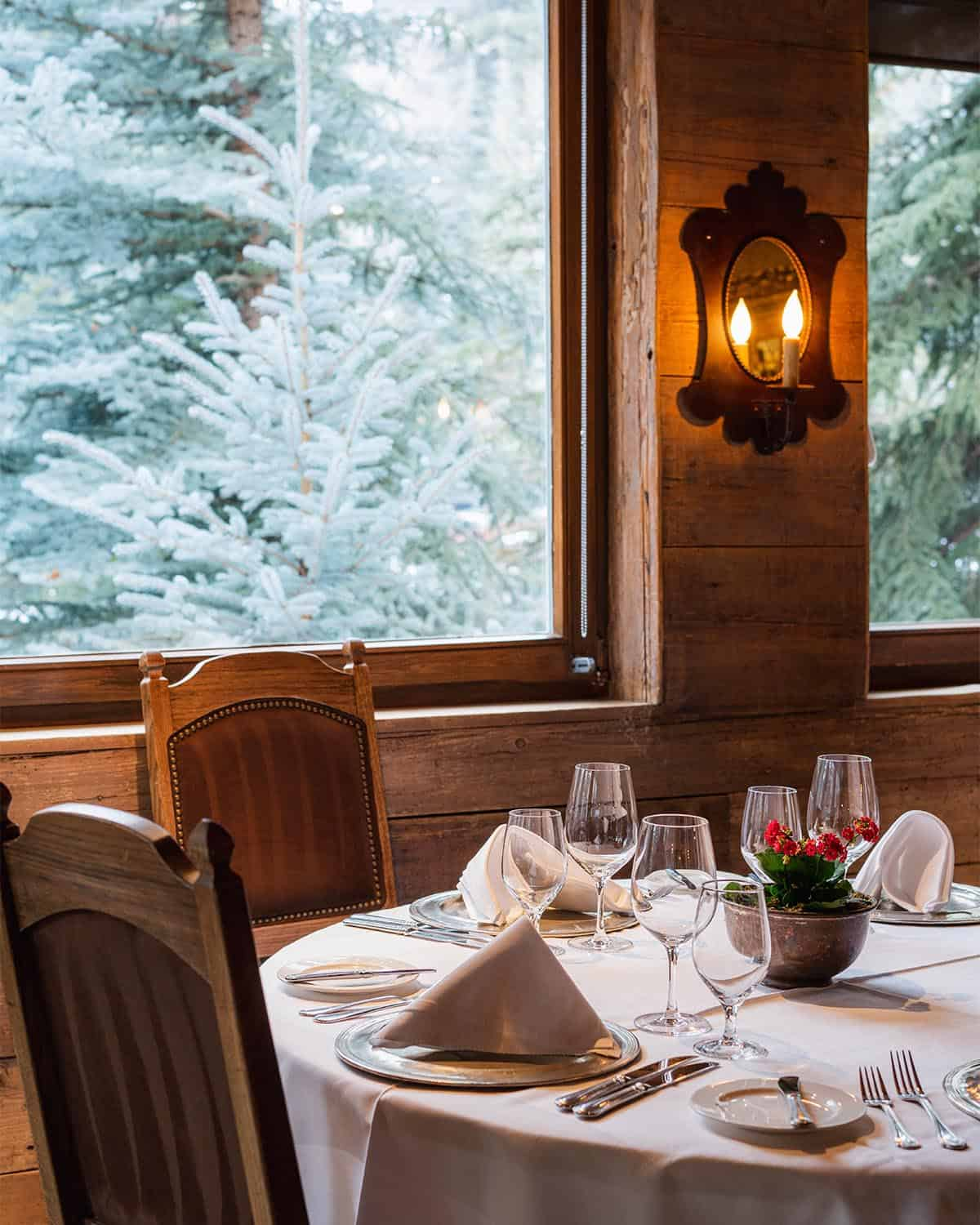 Round table set for dinner, chairs, next to window with view of snow-covered pine trees in the background