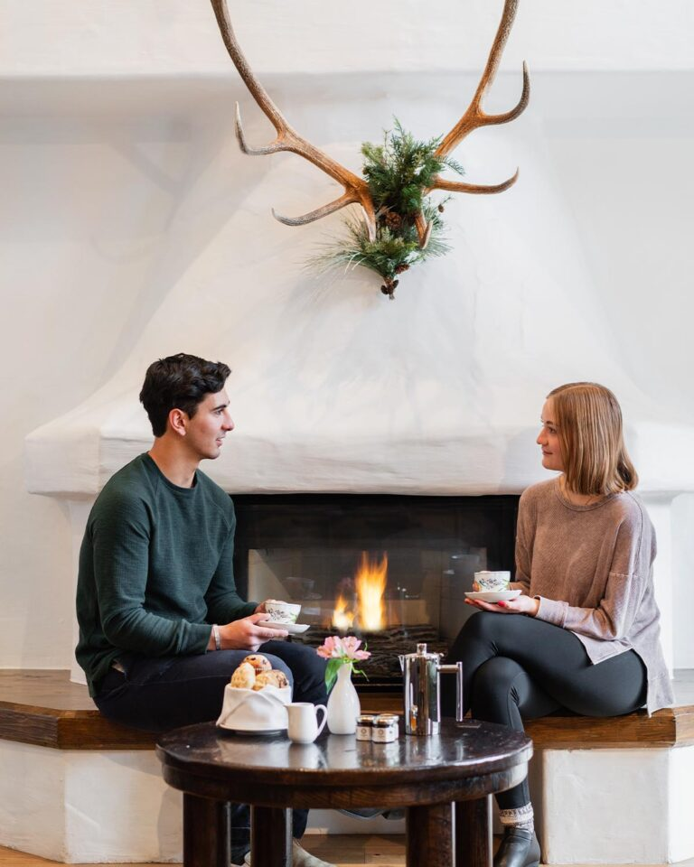 Couple holding cups, sitting next to fireplace with antlers on the wall above, and table with pastries and kettle in the foreground