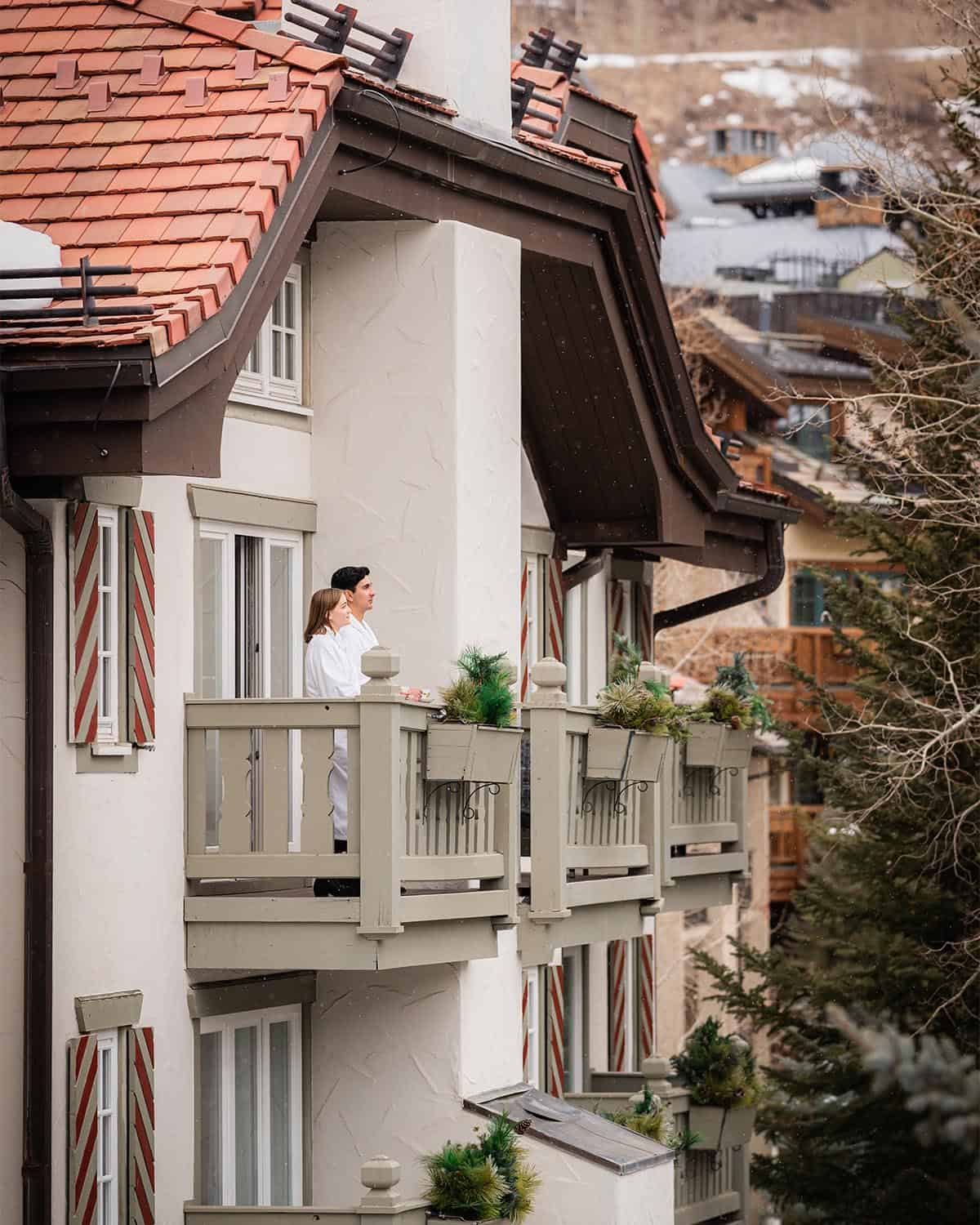 Couple on hotel balcony, wearing robes, and pine tree in the foreground