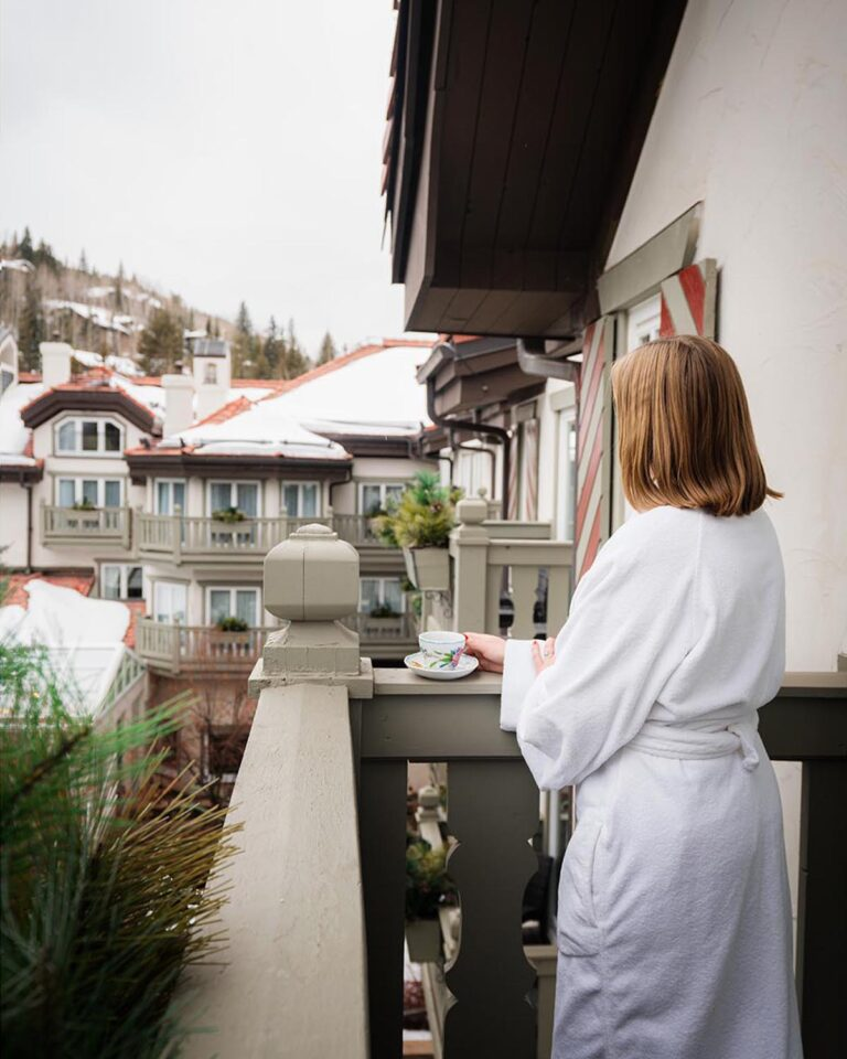 Woman wearing bathrobe, on a balcony, holding cup of coffee and looking over at snow-covered rooftops