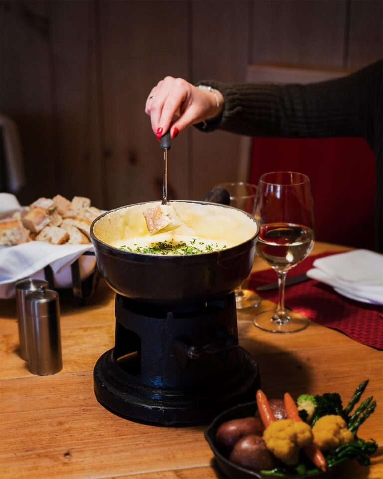 Woman dipping bread into fondue pot at table