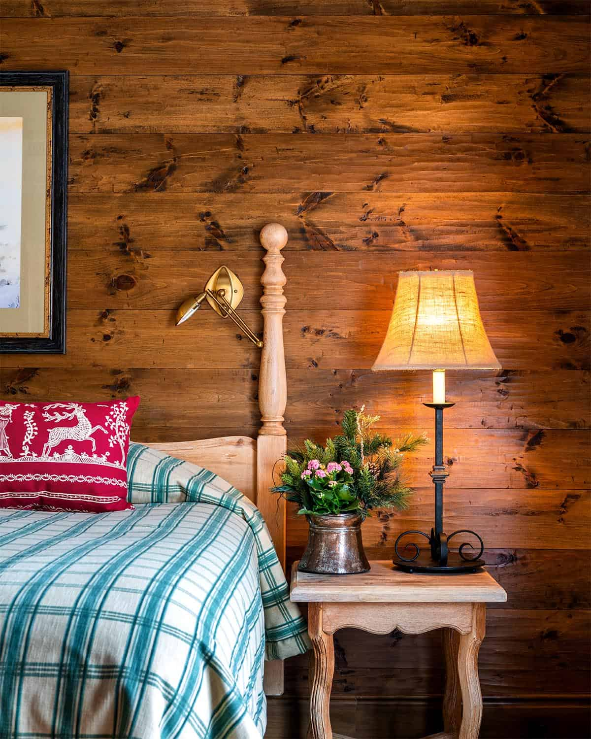 Hotel bed, nightstand with lamp, and wood-paneled wall