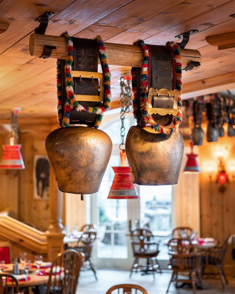 Two cowbells attached to leather belts, hanging from restaurant's dining area ceiling