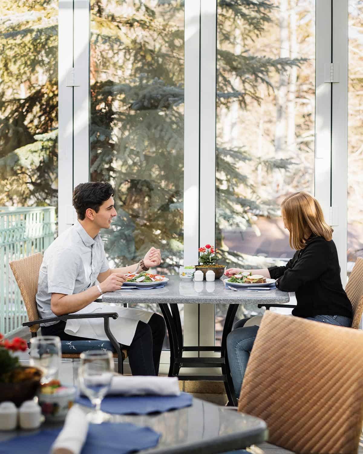 Couple enjoying a meal, sitting at covered outdoor restaurant area with large glass doors with view of trees