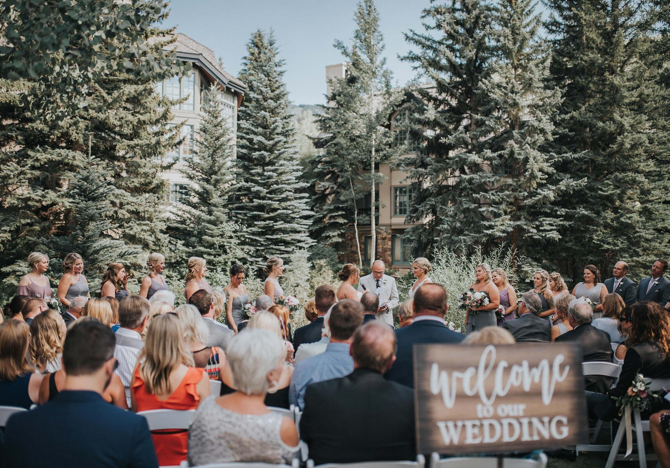Wedding ceremony outdoors, pien trees and hotel in the background