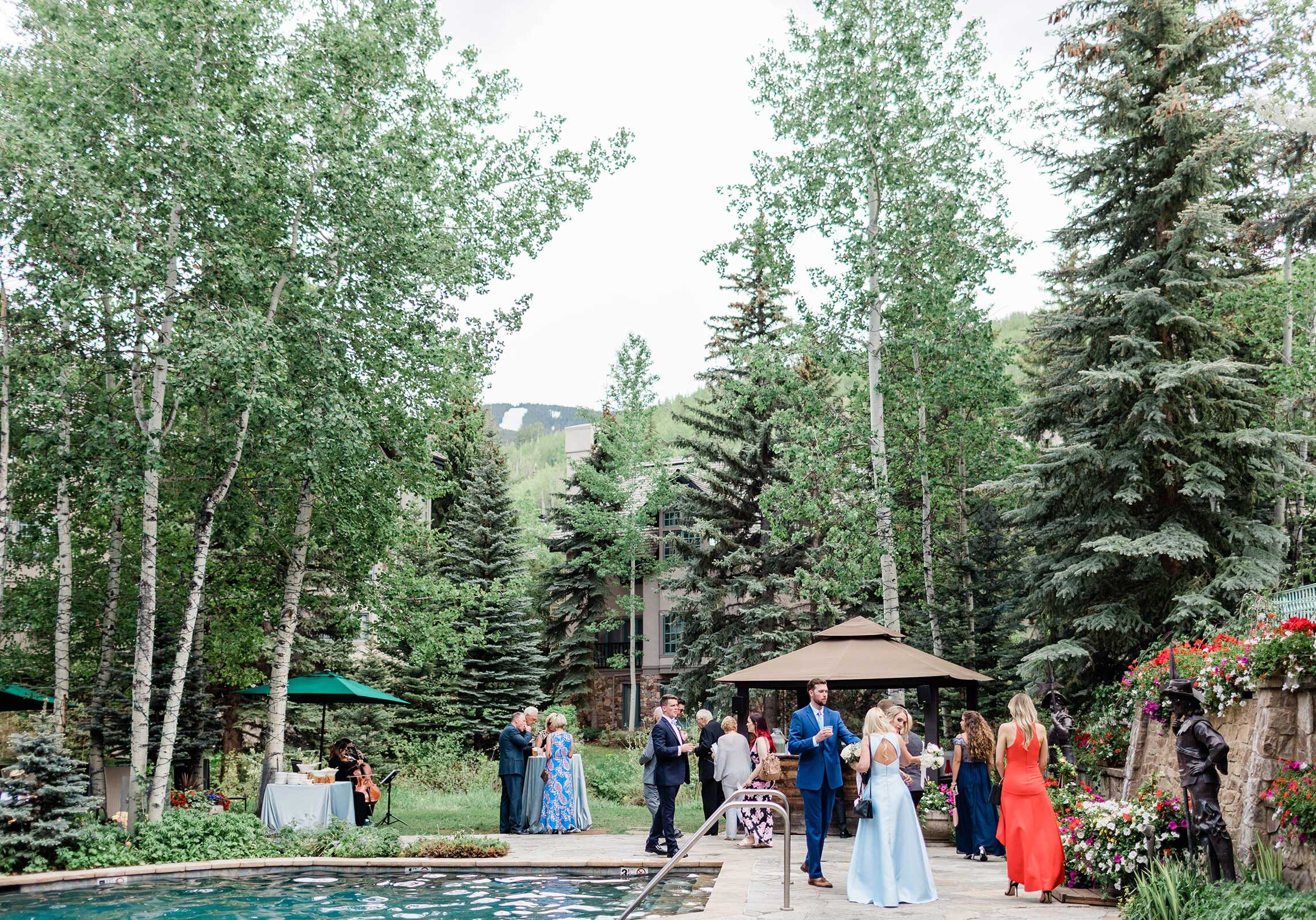 People elegantly addressed standing around a pool, drinking cocktails